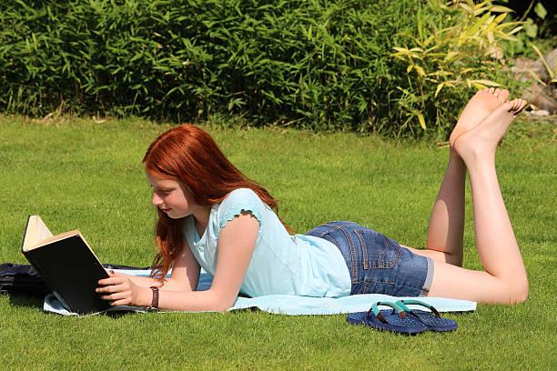 Bild von jungen Mädchen lesen Schule Buch auf Garten Rasen – Foto