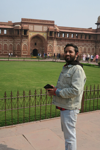 Image of young handsome Hindu man in early 20s standing in front of historic Mughal Agra Fort posing with mobile in his hand wearing denim jacket, pulling double denim look at Agra, India man smiling, posing with hair brushed back, brown beard, T-shirt