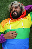Stock photo of young handsome Hindu man wearing rainbow gay LGBT flag hoodie posing with hand under head. In early 20s looking sideways smiling with short beard and dyed bleached messy blonde hair, closeup portrait of good looking guy from Delhi, India wearing rainbow hoodie outside in park lying on grass.