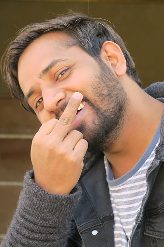 Image of young handsome Indian hoodie man smiling and holding up middle fingers as funny rude insult, good looking Hindu man with beard messing about on holiday vacation, wearing black hoodie, blue white T-shirt, India