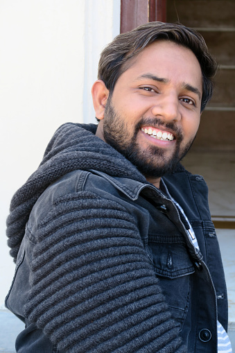 Image of young handsome Indian man being silly and laughing, happy hindu man in early 20s smiling and grinning sitting on staircase at holiday having fun pulling funny face, man with beard messing about, wearing black hoodie, blue white t-shirt.