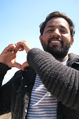 Image of young Hindu Indian hoodie man with love heart hands forming silhouette shape against sun and blue sky, heart hand shape formed with fingers as concept wallpaper photo for couple's love, romance and wedding theme with Valentine's Day heart symbol