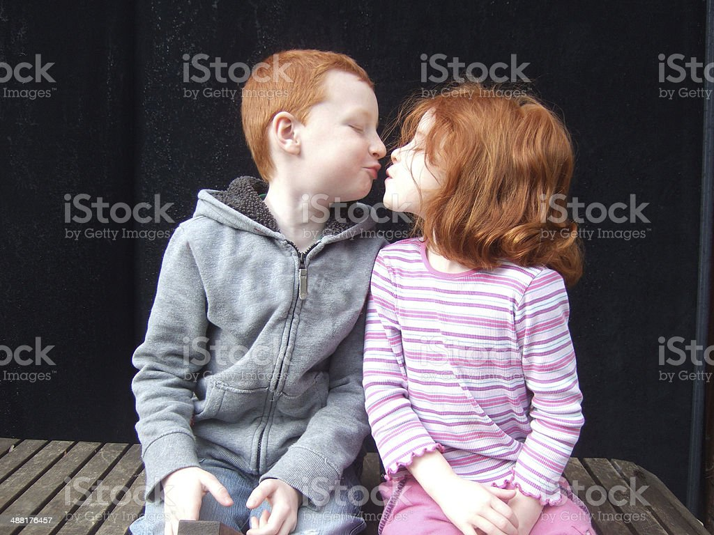 Image of young loving red-haired children kissing as they pose stock photo