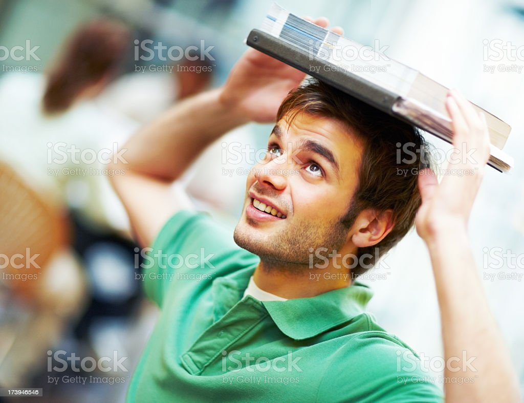 Image of young smiling man balancing books on his head royalty-free stock photo