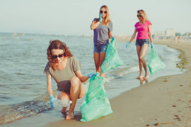 Image of young women volunteers picking up (cleaning) plastic garbage on the beach - save the earth, ecology and plastic recycling concept