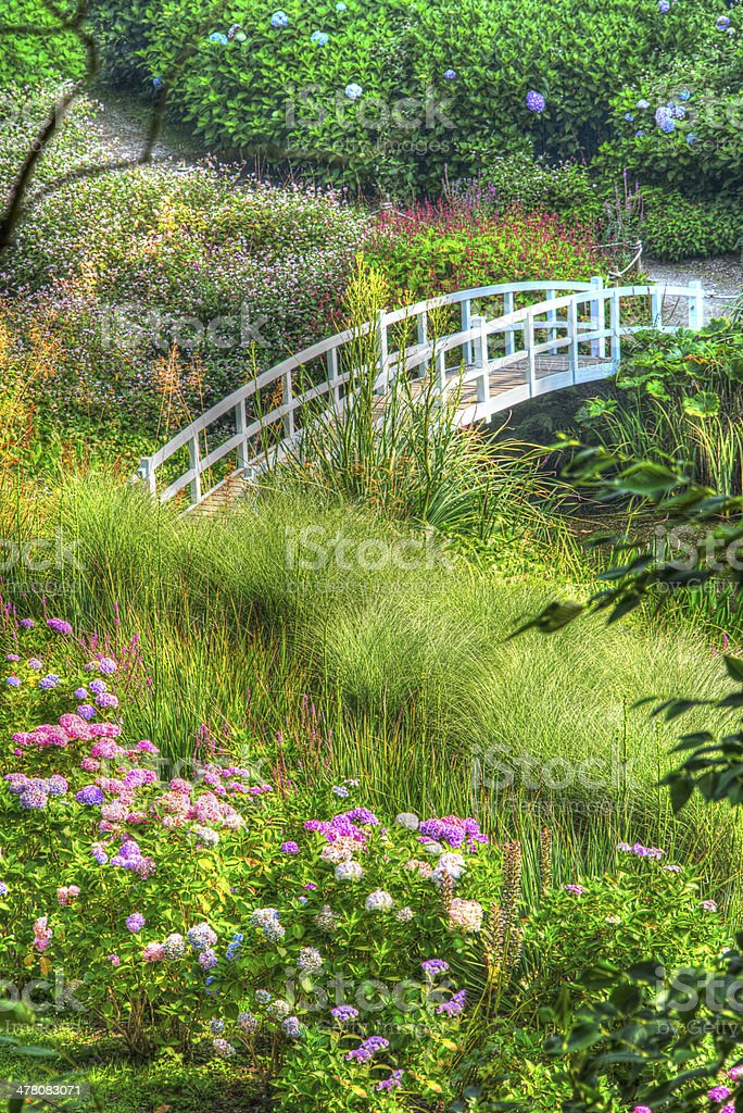 HDR Image Ornate Gardens bridge, valley of trees and flowers stock photo