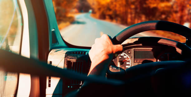 Image related to road trips.Detail of man's hand at the wheel stock photo