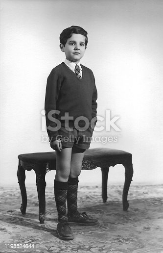 Image taken in the 60s, caucasian boy posing standing looking away studio shot