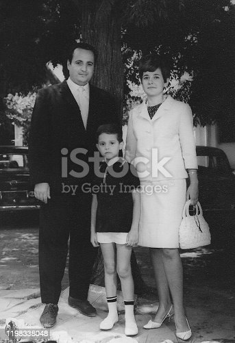 black and white image taken in the 60s: child boy posing with his parents