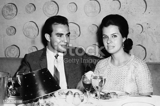 Black and white Image taken in the 60s - hispanic young man posing with his caucasian young girlfriend having dinner sitting in a restaurant table