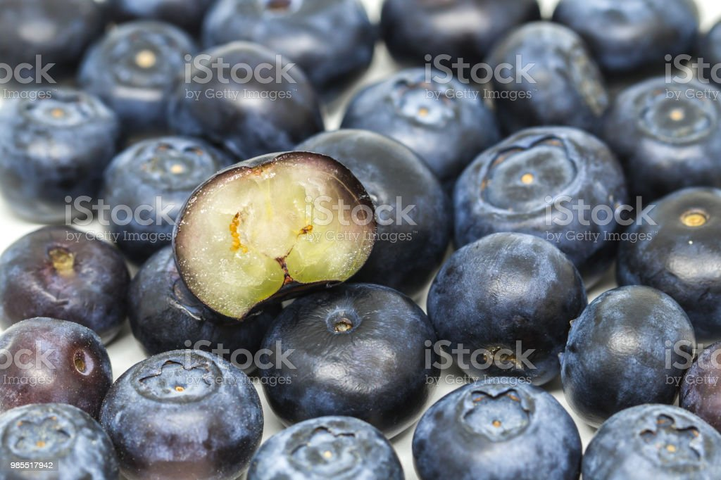 Image with a group of lined ripe blueberries. Half cut blueberry stock photo