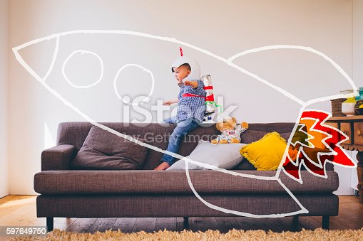 Little boy dressed as a spaceman sitting on back of a sofa. A vector animated drawing of a rocket as if he is travelling in it. Pretend play.