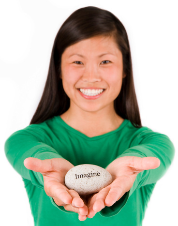 Young Asian woman generously offering the gift of an affirmation rock engraved with the word Imagine.  Very narrow dof with focus on rock and hands and face out of focus.