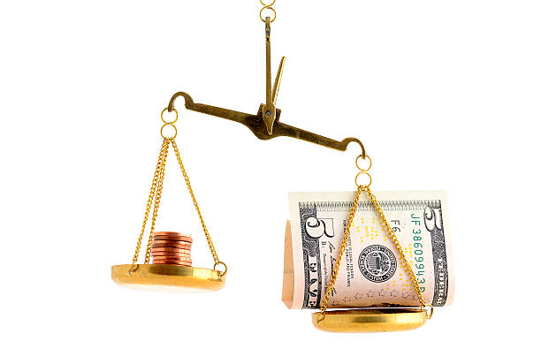 Imbalance betweeen dollar bill and copper coins on scale stock photo