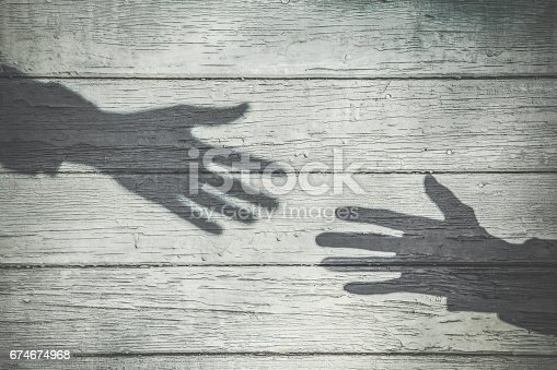 istock Imitation. Dark shadows of hands reaching to each other on the wooden wall background. Vintage style. 674674968