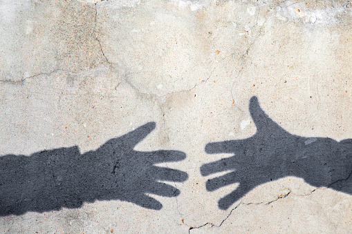 istock Imitation. Dark shadows of hands reaching to each other. 618645414