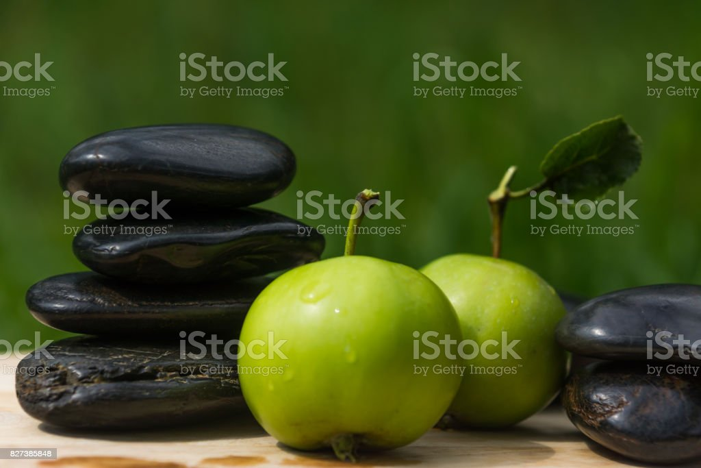 immature green apple and black pebbles on a green background - concept of rejuvenation stock photo