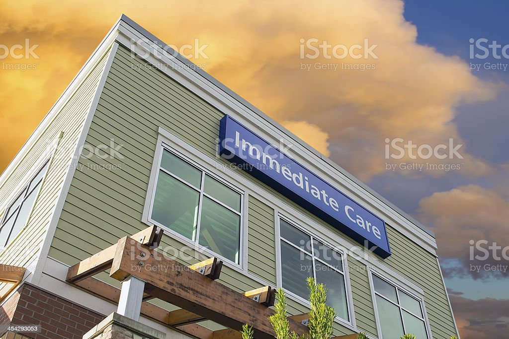 Immediate Care Sign On Hospital Building with Clouds stock photo