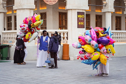 Doha / Qatar - February 18, 2020: immigrant man selling colorful globes for children in the streets of Souq Waqif