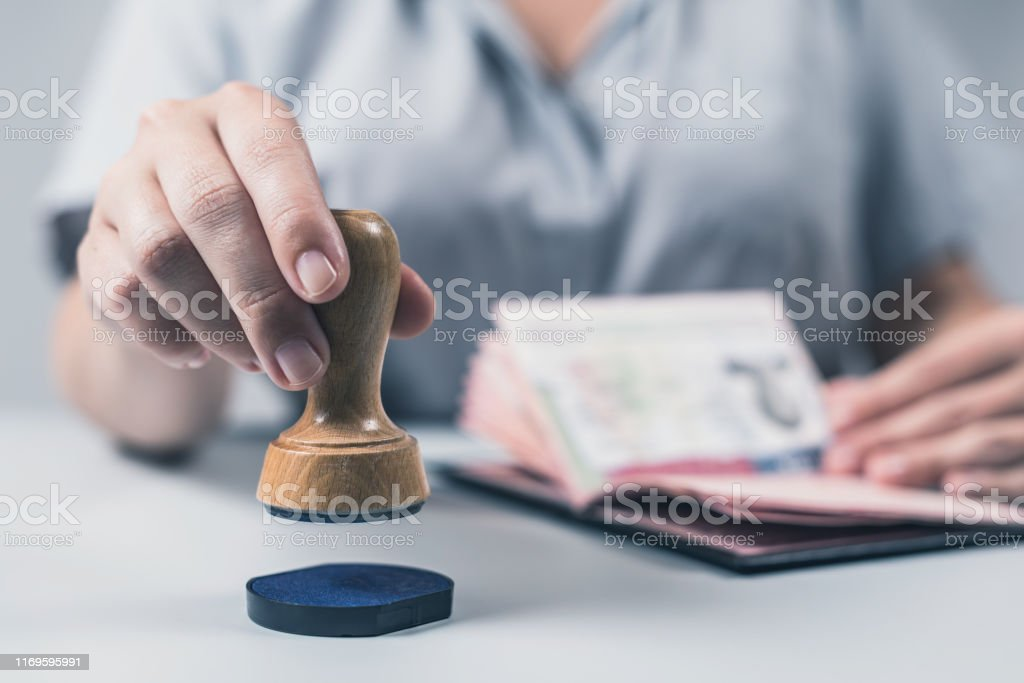 Immigration and passport control at the airport. woman border control officer puts a stamp in the US passport of american citizen. Concept Immigration and passport control at the airport. woman border control officer puts a stamp in the US passport of american citizen. Concept Adult Stock Photo