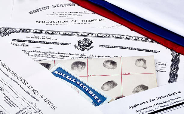 Immigration Documents US Certificate of Citizenship, declaration of intention, fingerpirnt card, social security card, application for naturalization and port of arrival manifest with red, white and blue ribbon citizenship stock pictures, royalty-free photos & images