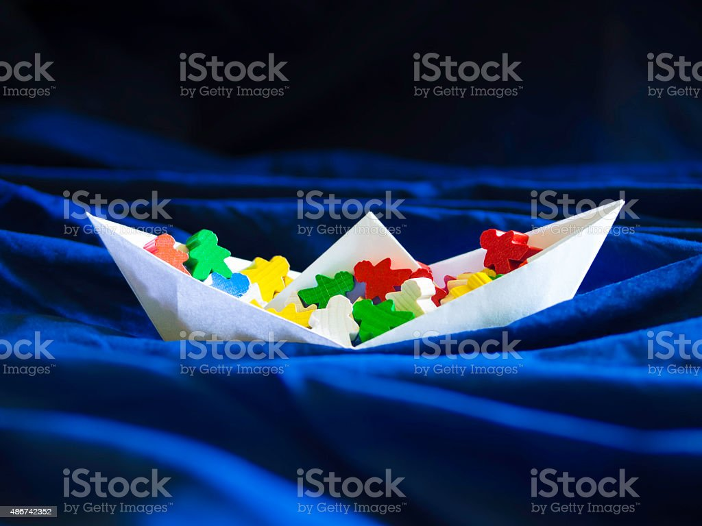 Immigration emigration migration concept, paperboat with meeples stock photo