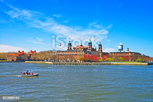 New York City, USA - April 25, 2015: Immigration station in Ellis Island, USA, and boat in Upper New York Bay. It was a gateway for immigrants who came to immigrant inspection. Tourists on board