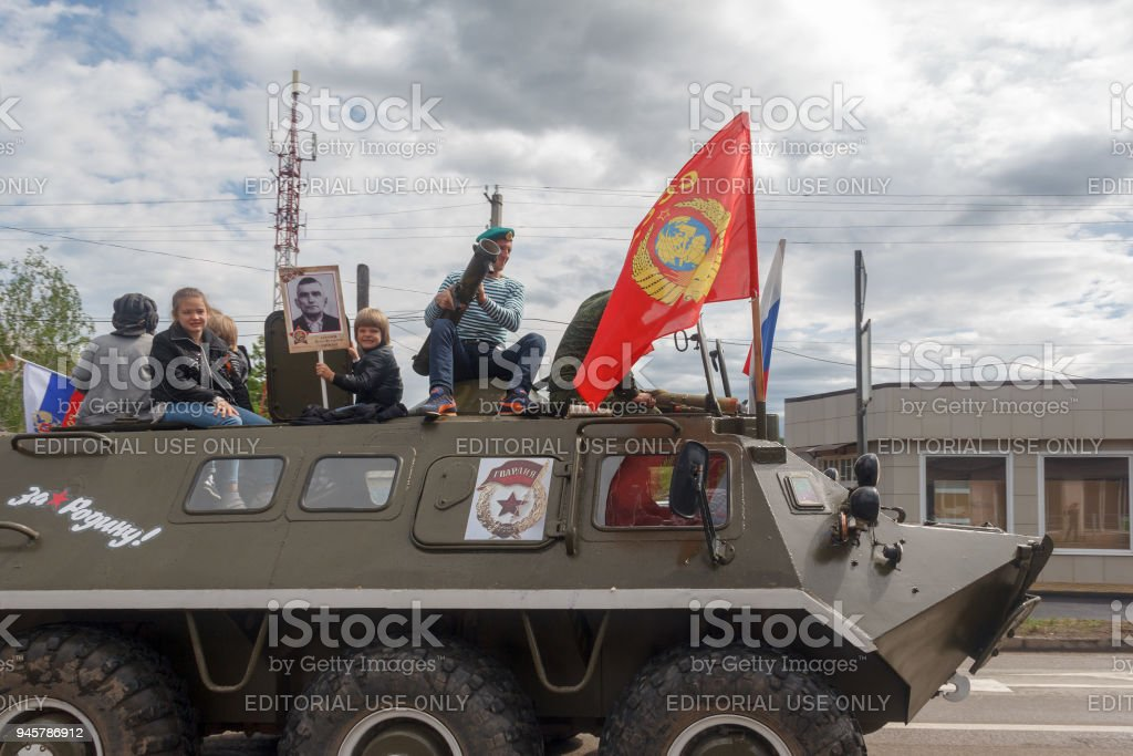 Immortal regiment, adults and children on an armored personnel carrier participate in parade in honor of victory day in Kamennomostsky settlement in Russia stock photo