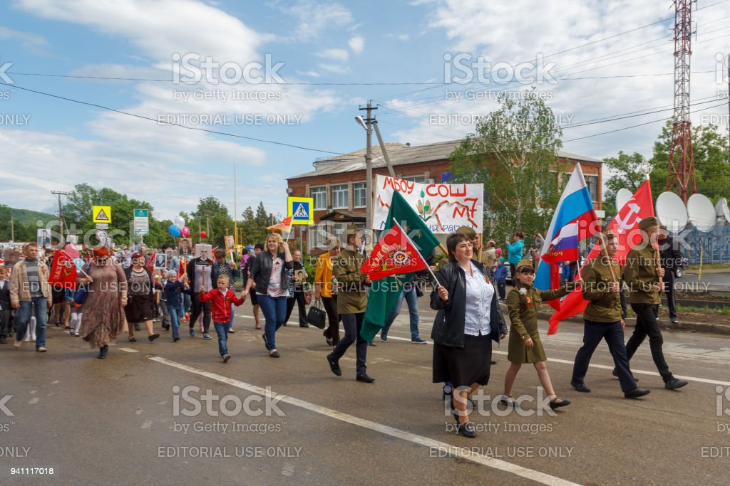 Adygea, Russia - May 9, 2017: Immortal regiment, Parade with red flags on victory day with the participation of schoolchildren and parents stock photo
