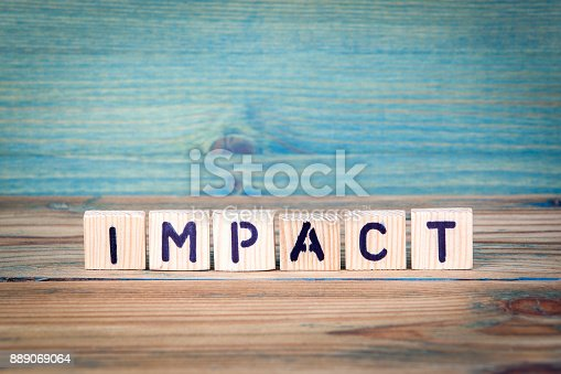 istock impact - name from wooden letters. Office desk, informative and communication background 889069064