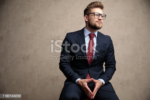 Impatient businessman looking hopefully to the side while wearing an elegant blue suit and glasses, sitting on a stool on wallpaper background