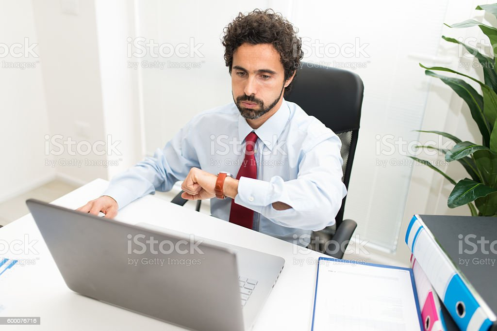 Impatient businessman snorting while watching his watch stock photo