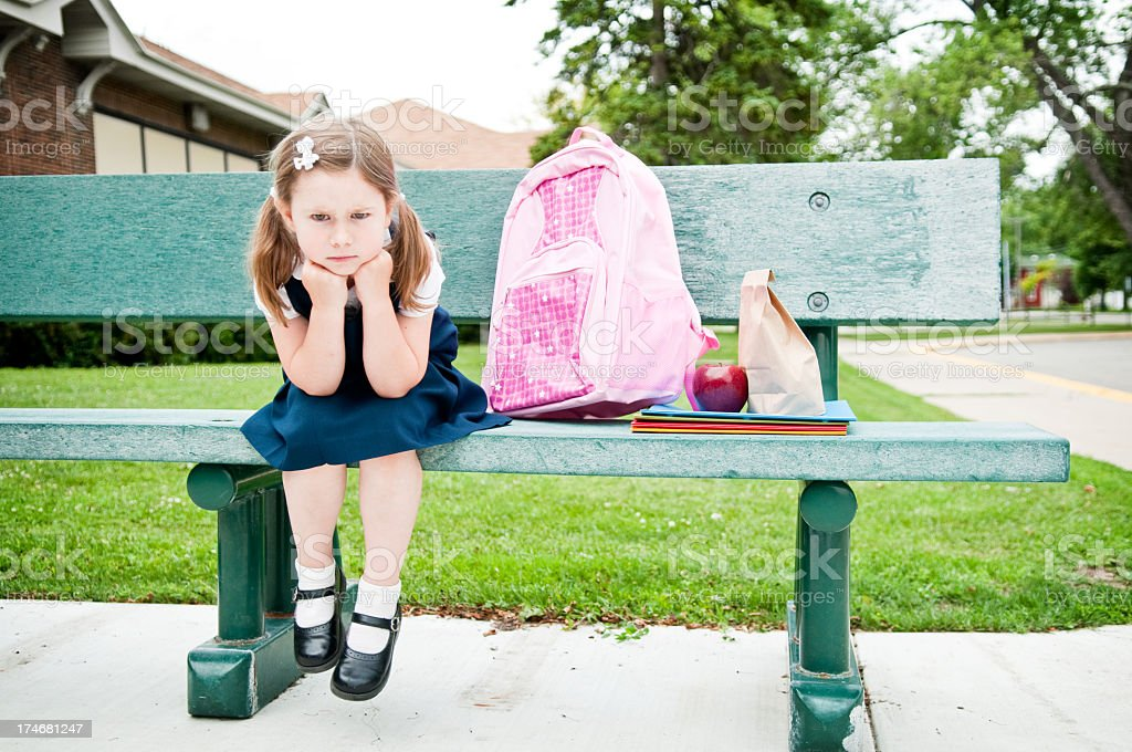 Impatient Little Girl Student Waiting on Bench for Her Parents stock photo