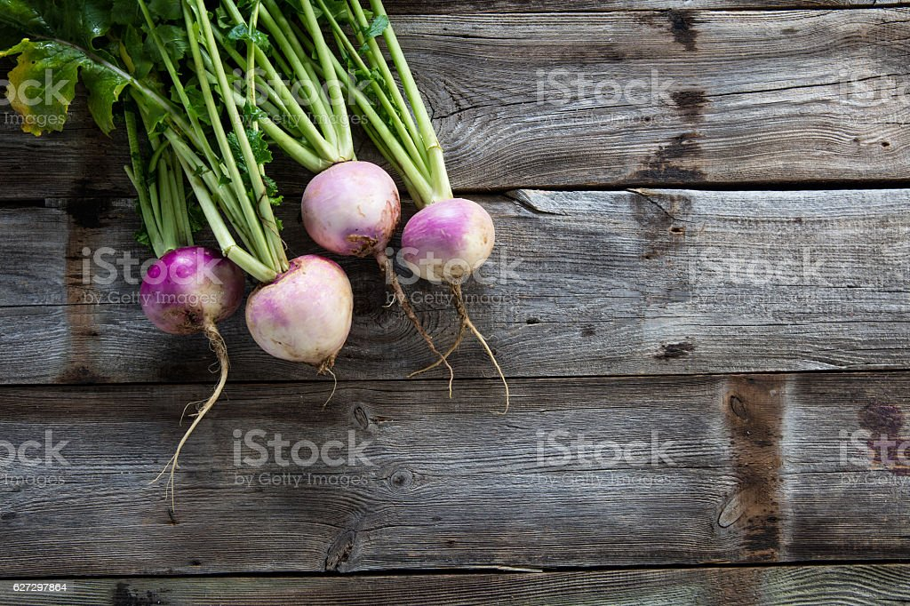 imperfect organic turnips, fresh green tops on authentic wood background stock photo