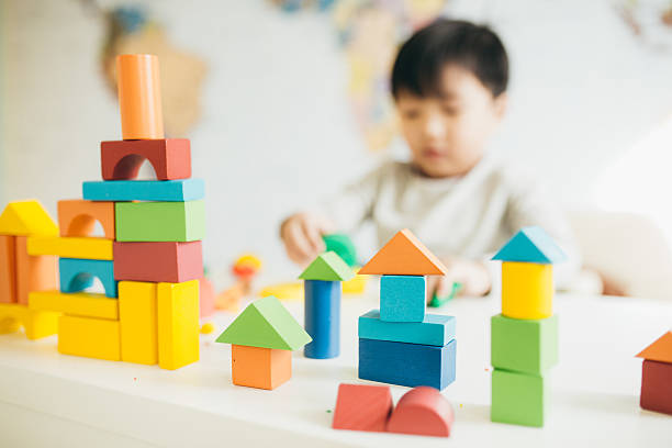 Importance of play in child development Focus on  wooden blocks and child on background autism stock pictures, royalty-free photos & images