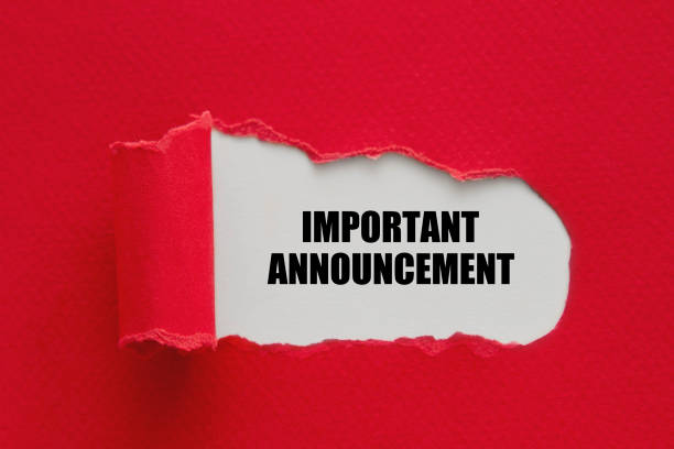 Important announcement written under torn paper. stock photo