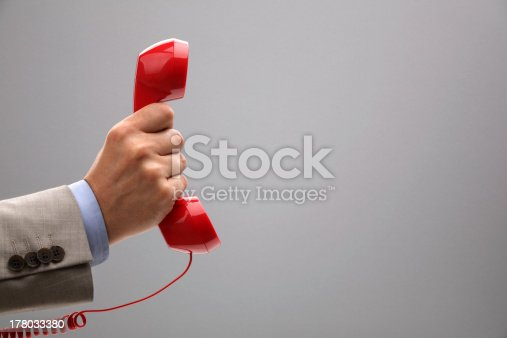 Red phone over gray background with copy space concept for customer support line or important call