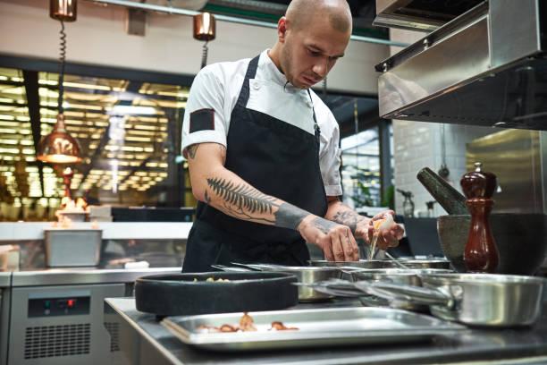 wichtiger bestandteil. konzentrierter junger koch bricht ein ei für traditionelle italienische nudeln, während er in einer restaurantküche steht - italienische küchen dekor stock-fotos und bilder