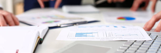 Important paper lie at table Important paper lie at table with group of colleagues in background closeup. Trade result, paperwork job, number balance, bank credit, loan money, invest payment, irs, commerce partnership concept letterbox format stock pictures, royalty-free photos & images