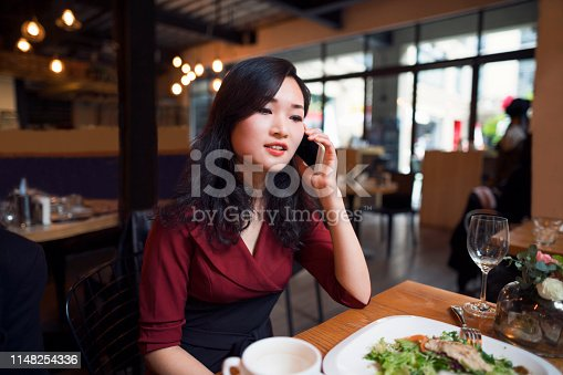 Young beautiful Chinese ethnicity businesswoman having lunch in a restaurant and talking on the phone.