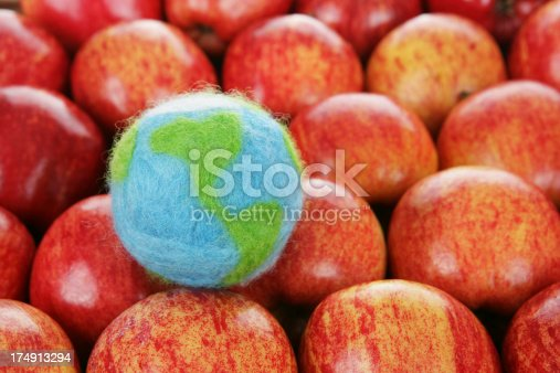 A background of apples with a small felted world (made by me).