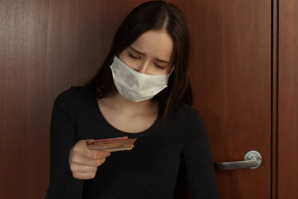 Imposing a fine for leaving the house with a coronavirus. Sad young woman in a medical mask holds in her hands payment in euros stock photo