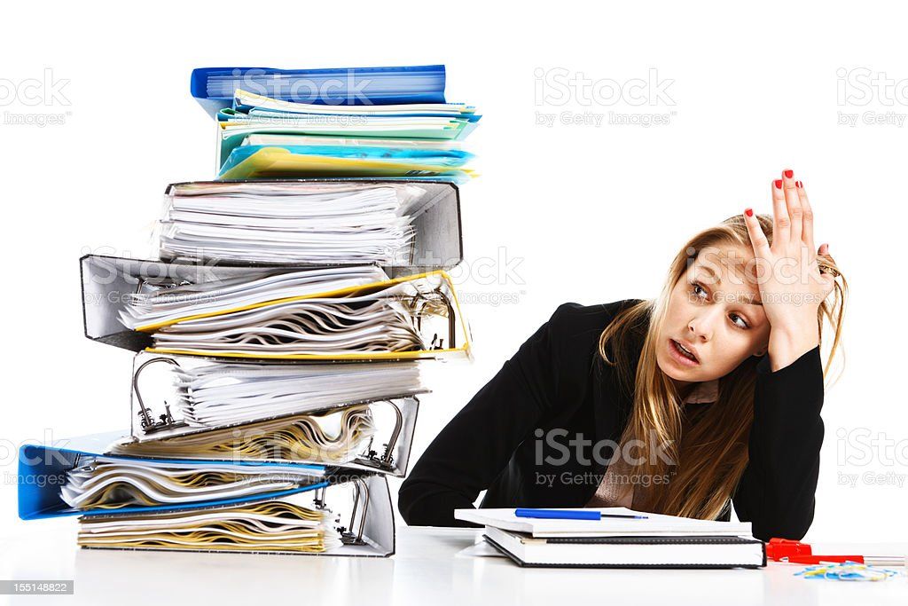 Impossible amount of work overhelms unhappy young businesswoman royalty-free stock photo