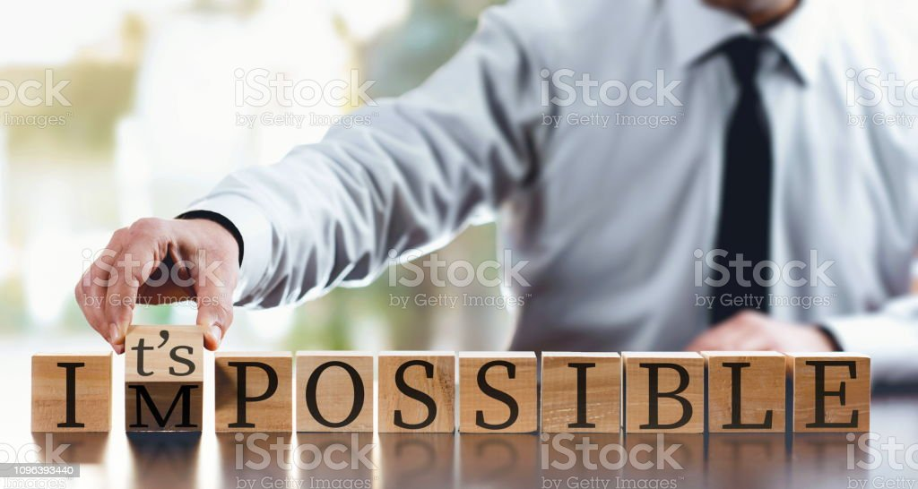 Impossible Concept With Businessman and  Wooden Blocks Impossible Concept With Businessman and  Wooden Blocks Achievement Stock Photo