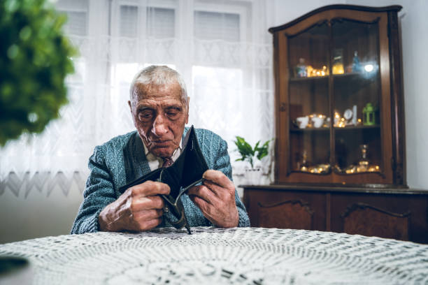 Impoverished man Old caucasian man holding empty wallet. empty wallet stock pictures, royalty-free photos & images