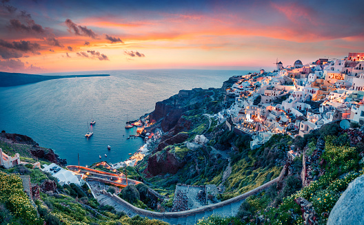 Impressive evening view of Santorini island. Picturesque spring sunset on the famous Greek resort Oia, Greece, Europe. Traveling concept background. Artistic style post processed photo.