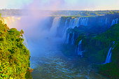 Impressive Iguacu falls at gold colored sunset, one of the most beautiful waterfalls in the world and one of the seven Wonders of Nature, dramatic beauty in nature landscape - Idyllic Devil's Throat - international border of Brazilian Foz do Iguacu city, Parana State, Argentina Puerto Iguazu city, Misiones province and Paraguay - rainforest landscape panorama, South America