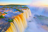 Impressive Iguacu falls, one of the most beautiful waterfalls in the world and one of the seven Wonders of Nature, blurred motion from long exposure at dramatic sunset - Idyllic Devil's Throat - international border of Brazilian Foz do Iguacu city, Parana State, Argentina Puerto Iguazu city, Misiones province and Paraguay - rainforest landscape panorama, South America