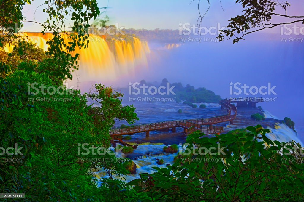 Impressive Iguacu falls landscape, blurred motion from long exposure at dramatic sunset - Idyllic Devil's Throat - international border of Brazilian Foz do Iguacu, Parana, Argentina Puerto Iguazu, Misiones and Paraguay - South America