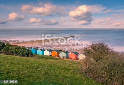 Impressive winter clouds in a cool blue sky over the beach huts and natural spit of land that stretches out to sea on the beach in Tankerton, Whitstable, Kent, UK. A three people are strolling on the natural and locally named  'Street'